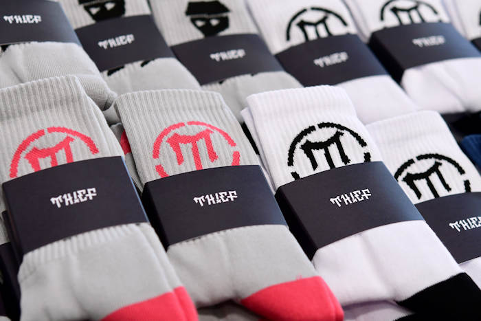 Omalla logolla kudotut sukat ja painettu pakkaus